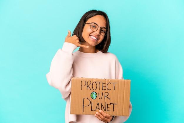 De jonge spaanse gemengde rasvrouw die beschermt onze planeetkarton houdt een mobiel telefoongesprekgebaar met vingers toont.