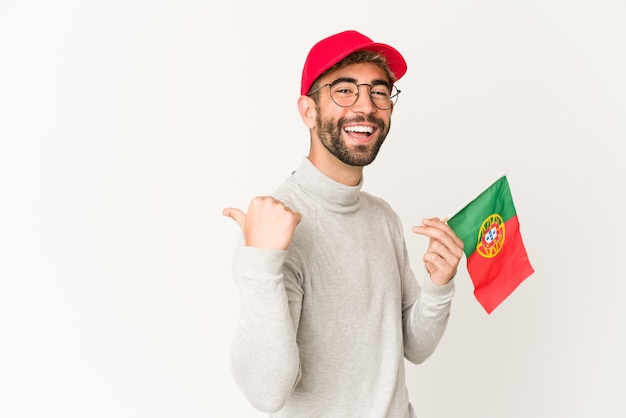 De jonge spaanse gemengde rasvrouw die een vlag van portugal houdt wijst met duimvinger weg, lachend en zorgeloos.