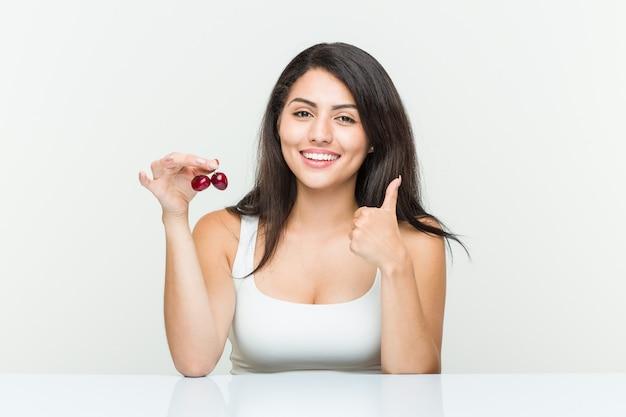 De jonge spaanse kersen die van de vrouwenholding en duim glimlachen verhogen