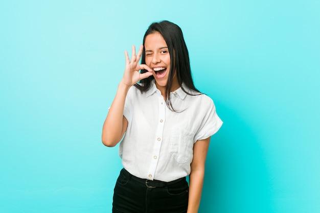 De jonge spaanse koele vrouw tegen een blauwe muur knipoogt een oog en houdt een ok gebaar met hand.