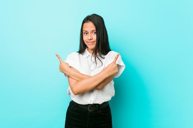 De jonge spaanse koele vrouw tegen een blauwe muur wijst zijdelings, probeert tussen twee opties te kiezen.