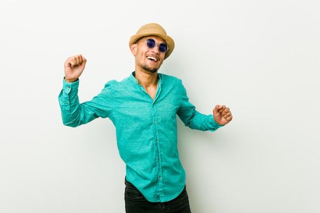 De jonge spaanse mens die de zomer draagt kleedt een speciale dag viert, springt en heft wapens met energie op.