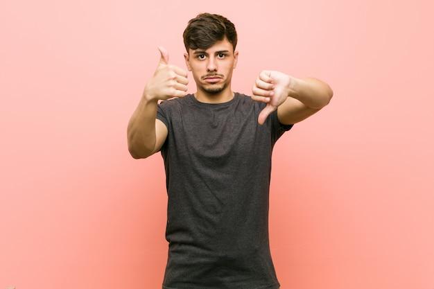 De jonge spaanse toevallige mens die duimen tonen en duimen neer, kiest moeilijk concept