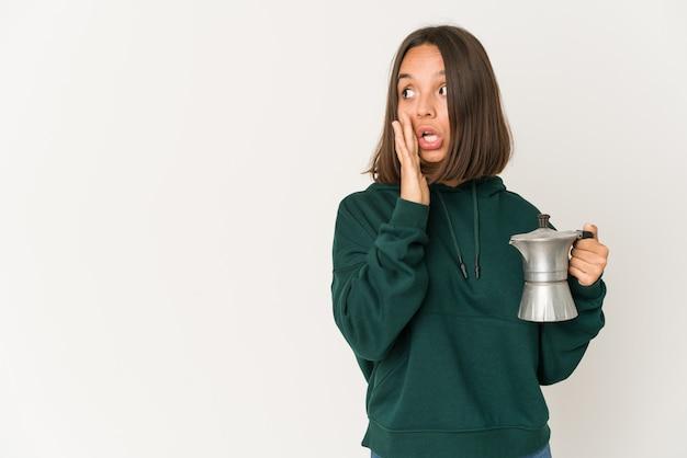 De jonge spaanse vrouw die een koffiezetapparaat houdt zegt een geheim heet remmend nieuws en kijkt opzij