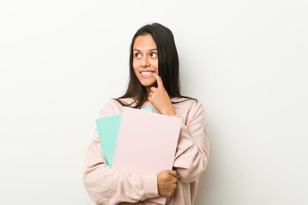 De jonge spaanse vrouw die sommige notitieboekjes houden ontspande het denken over iets bekijkend een exemplaarruimte.