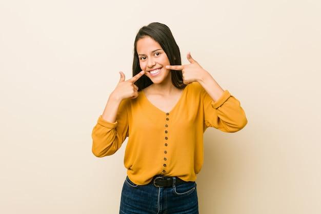 De jonge spaanse vrouw tegen een beige muur glimlacht, wijzend vingers op mond.