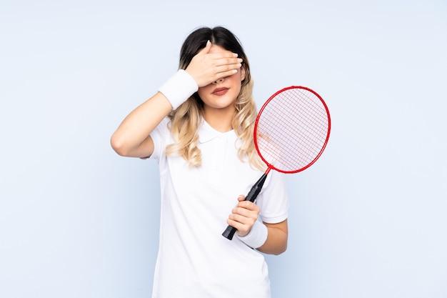 De jonge speler van het vrouwentennis op geïsoleerde muur