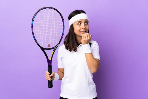 De jonge speler van het vrouwentennis over geïsoleerde zenuwachtig en doen schrikken achtergrond die handen aan mond zetten