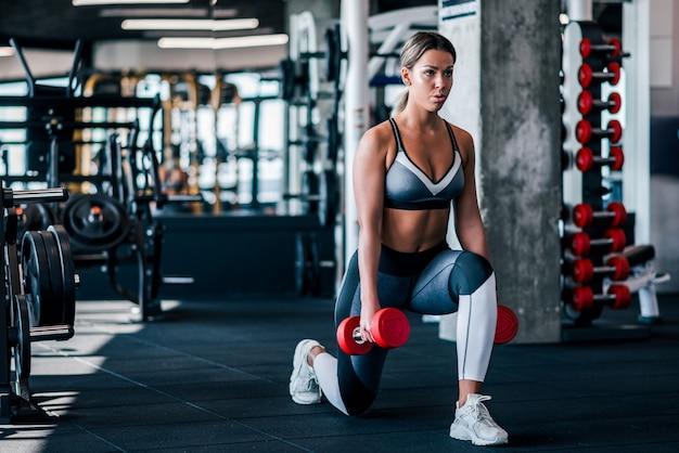 De jonge spiervrouw die lunges doen oefent met domoren in de gymnastiek uit.