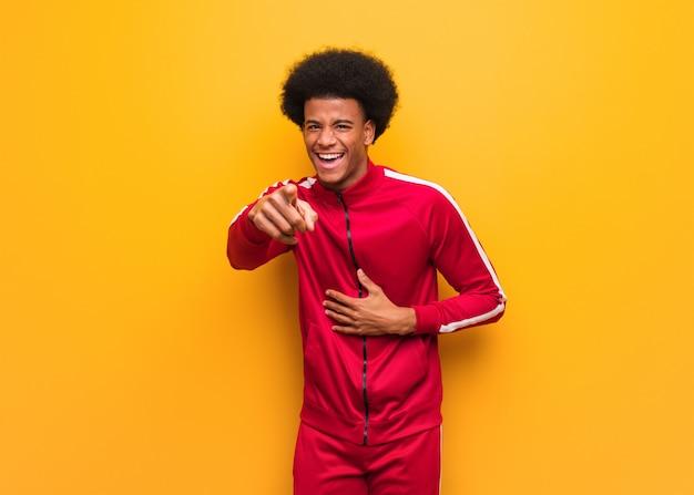 De jonge sport zwarte mens over een oranje muur droomt van het bereiken van doelen en doeleinden