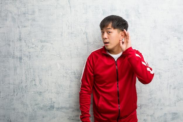 De jonge sportfitness chinees probeert aan het luisteren van een roddel