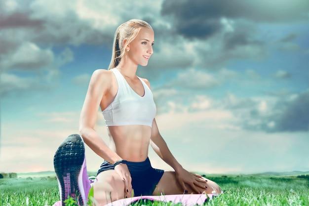 De jonge sportieve vrouw die van de geschiktheidsspier roze mat houden en aan muziek luisteren.