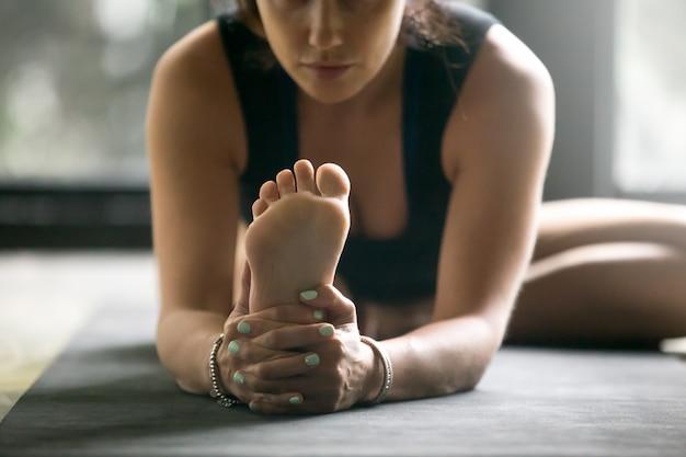De jonge sportieve vrouw in janu sirsasana stelt, studioachtergrond