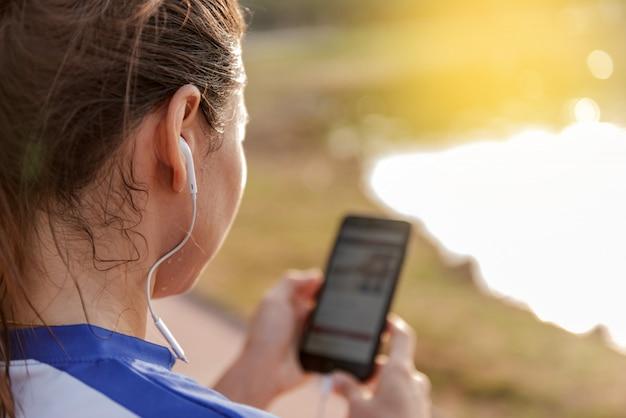 De jonge sportieve vrouw luistert aan muziek via een smartphone en earbuds