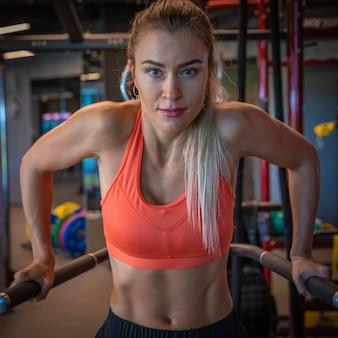 De jonge sportieve vrouw versterkt met domoren in gymnastiek