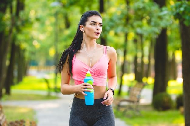 De jonge sportvrouw die in het park loopt