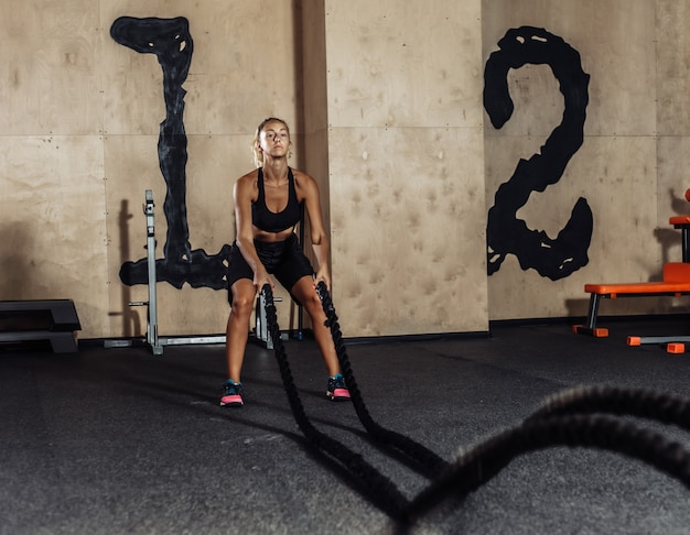 De jonge sportvrouw in sportkleding leidt met slagtouw op in de gymnastiek. functionele training. gezonde levensstijl concept