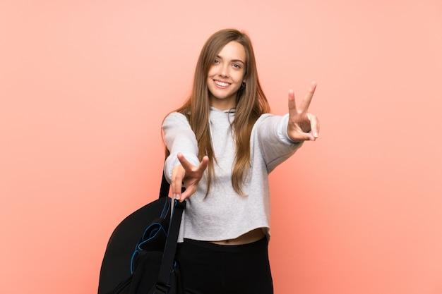 De jonge sportvrouw isoleerde roze glimlachend en overwinningsteken tonend