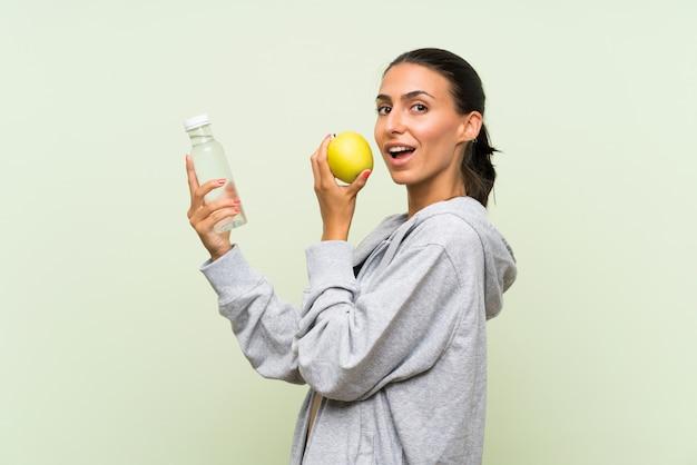 De jonge sportvrouw met een appel en met een fles waterover isoleerde groene muur