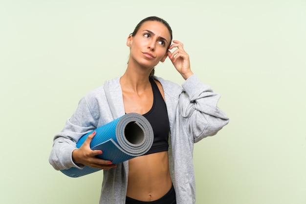 De jonge sportvrouw met mat over geïsoleerde groene muur die twijfels hebben en verwart gezichtsuitdrukking