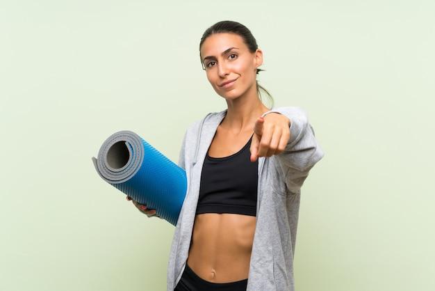 De jonge sportvrouw met mat over geïsoleerde groene muur richt vinger op u met een zekere uitdrukking