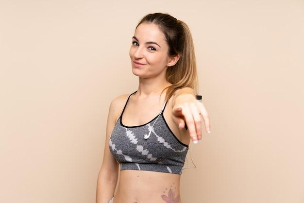 De jonge sportvrouw over geïsoleerde muur richt vinger op u met een zekere uitdrukking