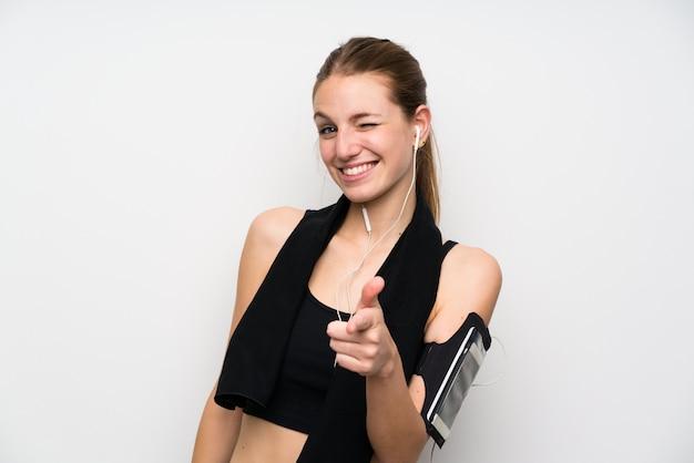 De jonge sportvrouw over geïsoleerde witte muur richt vinger op u
