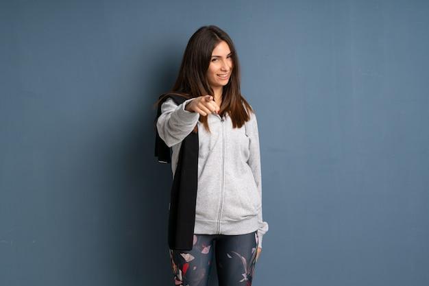 De jonge sportvrouw richt je vinger op je met een zelfverzekerde uitdrukking