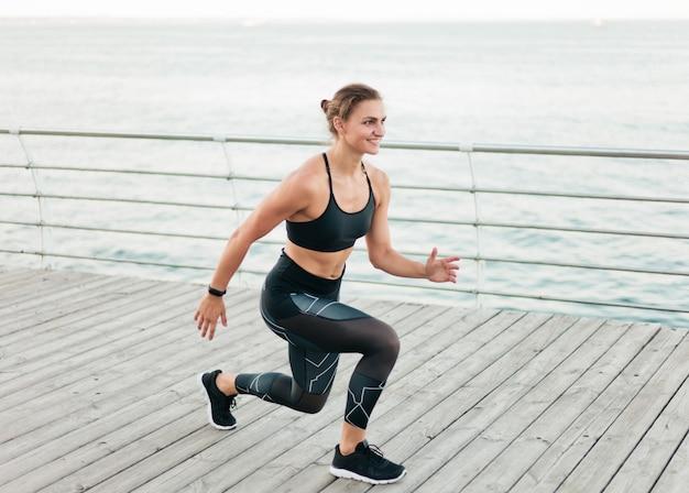 De jonge sportvrouw valt op het strandterras uit