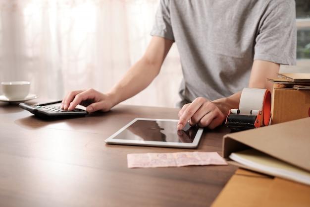 De jonge startbedrijfseigenaar controleert orde op tablet in de ochtend