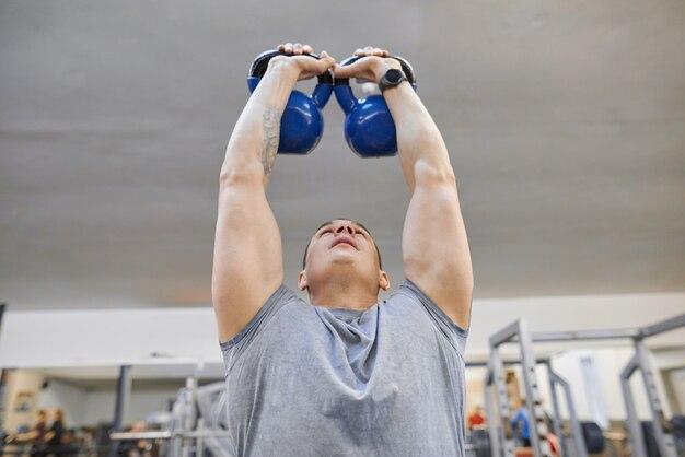 De jonge sterke gespierde atletenbodybuilder heft gewichten in de gymnastiek op