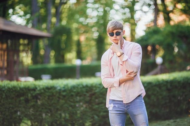 De jonge stijlvolle knappe man in vrijetijdskleding en zonnebrillen en klok staat op de campus