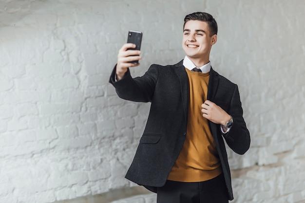 De jonge stijlvolle zakenman maakt een selpie op kantoor en glimlacht