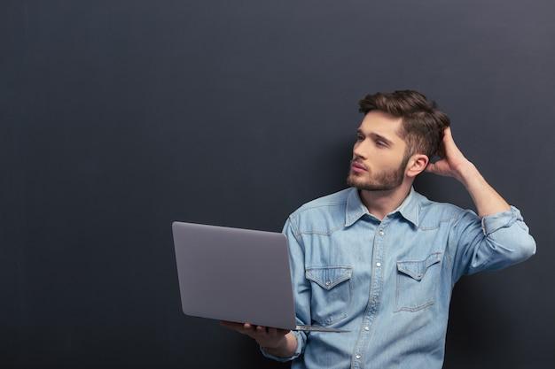 De jonge student in jeansoverhemd gebruikt laptop.