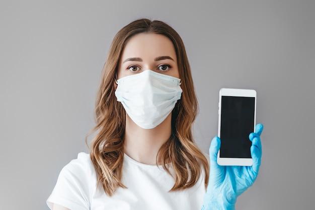 De jonge studente in medisch masker dat op grijze achtergrond wordt geïsoleerd toont een mobiele telefoon, een mockup, een exemplaarruimte voor tekst of ontwerp