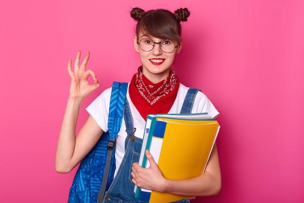 De jonge studentenvrouw die ok teken toont, heeft goed resultaat van examen.