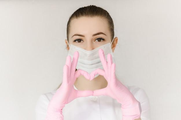 De jonge succesvolle arts in beschermend masker en witte laag toont teken met harthand
