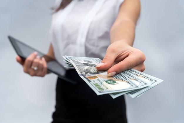 De jonge succesvolle dollarbiljetten van de bedrijfsvrouwenholding en het gebruiken van tablet geïsoleerde grijze achtergrond.
