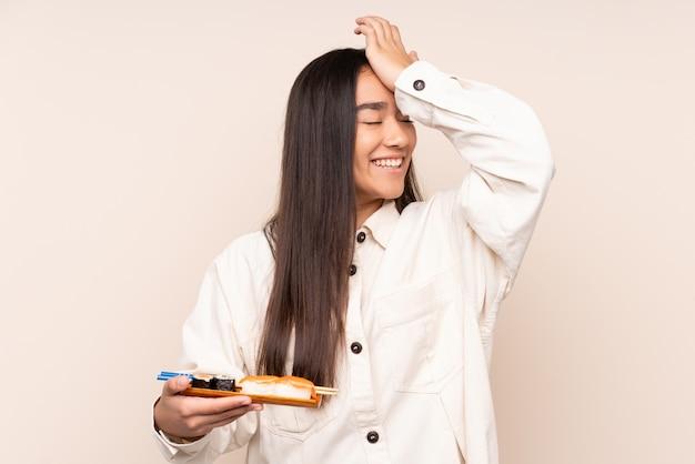 De jonge sushi van de vrouwenholding op beige heeft iets gerealiseerd en van plan de oplossing