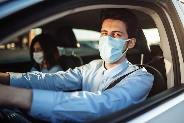 De jonge taxichauffeur van de jongen geeft passagier een rit die steriel medisch masker draagt.