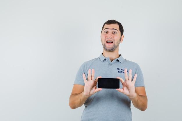 De jonge telefoon van de technicusholding met beide dient grijs uniform in en kijkt versuft, vooraanzicht.