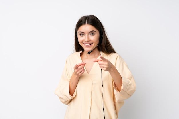 De jonge telemarketervrouw over geïsoleerde witte muur richt vinger op u