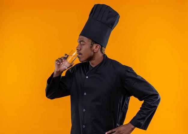 De jonge tevreden afro-amerikaanse kok in eenvormige chef-kok drinkt glas water dat op oranje muur wordt geïsoleerd