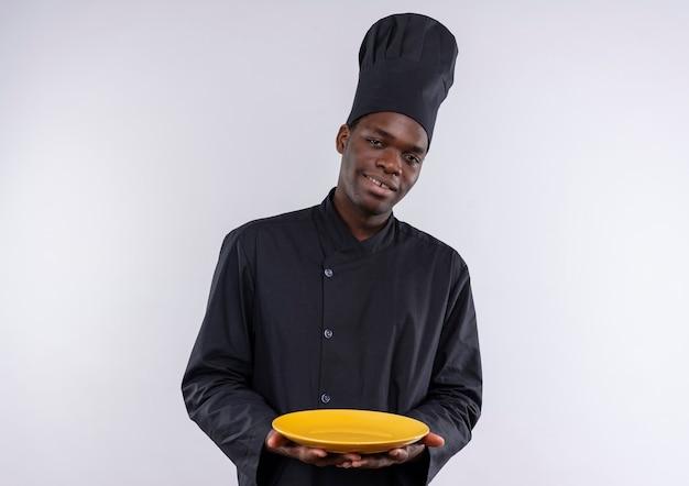 De jonge tevreden afro-amerikaanse kok in eenvormige chef-kok houdt plaat op beide handen op wit met exemplaarruimte
