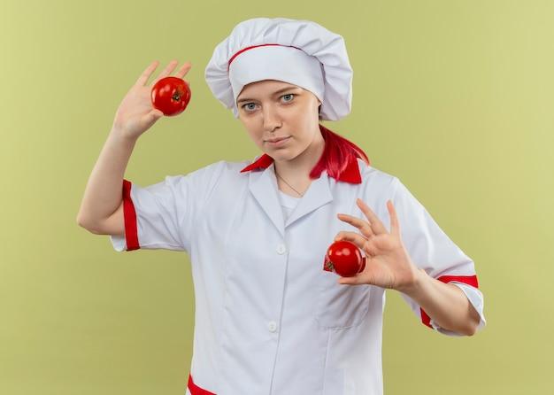 De jonge tevreden blonde vrouwelijke chef-kok in eenvormige chef-kok houdt tomaten die op groene muur worden geïsoleerd