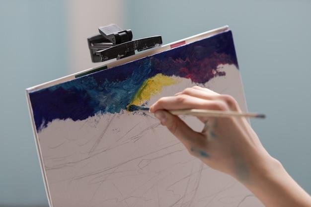 De jonge tienervrouwkunstenaar schildert een afbeelding op canvas met olieverf. close-up van het verfproces.