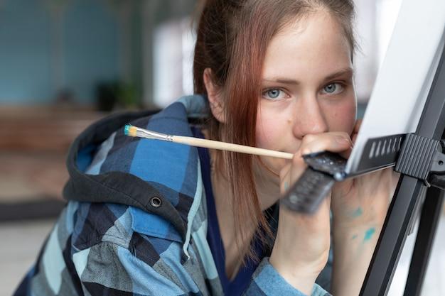 De jonge tienervrouwkunstenares met blauwe ogen houdt een penseel voor het schilderen met olieverf in haar hand. vrouw leunde op de ezel en keek