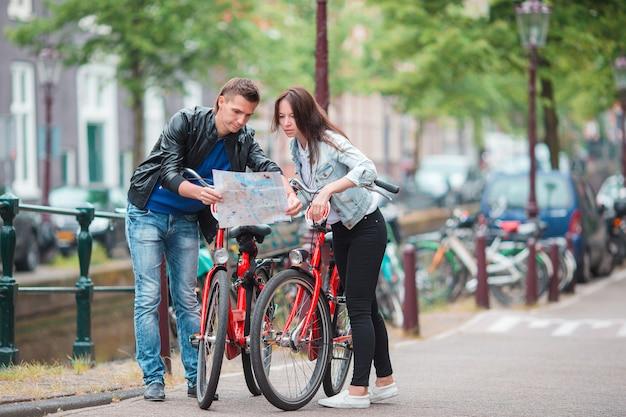 De jonge toeristen koppelen het bekijken kaart in europese stad. gezin van twee op vakantie in amsterdam