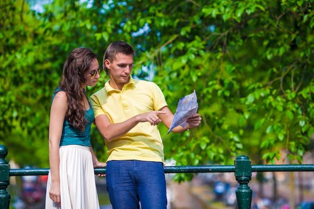 De jonge toeristen koppelen het bekijken kaart in europese stad