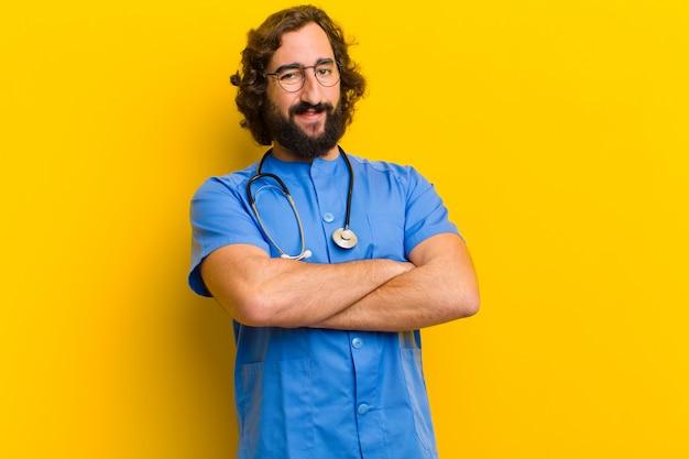 De jonge trotse verpleegstersmens stelt tegen gele achtergrond